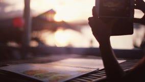 Mujer que toma la foto con el teléfono móvil de la puesta del sol mientras que se sienta en playa del café Ciérrese para arriba d almacen de video