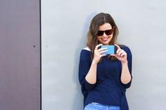 Mujer que toma la foto con el teléfono móvil por la pared Muchacha feliz en el CIT Foto de archivo