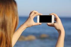 Mujer que toma la foto con una cámara elegante del teléfono Fotos de archivo libres de regalías