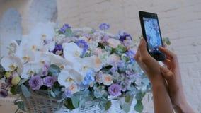 Mujer que toma la foto de la cesta floral grande con las flores con smartphone almacen de metraje de vídeo