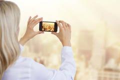 Mujer que toma la foto de la ciudad en luz de la mañana Fotografía de archivo