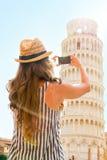 Mujer que toma la foto de la torre inclinada de Pisa, Italia Imagenes de archivo