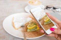 Mujer que toma la foto de su torta en café con el teléfono móvil Fotografía de archivo