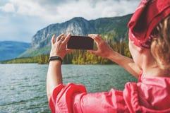 Mujer que toma la foto del lago y de la montaña Concepto del turismo foto de archivo