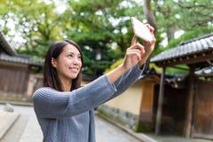 Mujer que toma la foto del selfie con el teléfono móvil Imagen de archivo
