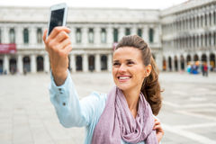 Mujer que toma la foto del uno mismo con el teléfono celular en Venecia Fotos de archivo libres de regalías
