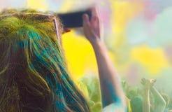 Mujer que toma la foto en el teléfono móvil en festival del color del holi Fotos de archivo