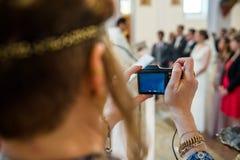 Mujer que toma la foto en la boda en iglesia Imágenes de archivo libres de regalías