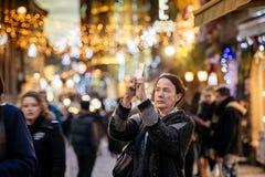 Mujer que toma la foto móvil de las decoraciones de la Navidad Imagen de archivo
