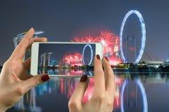 Mujer que toma la fotografía con una cámara elegante del teléfono en Marina Bay en Singapur Imagen de archivo