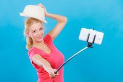 Mujer que toma la imagen de sí misma con el teléfono en el palillo imagen de archivo