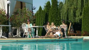 Mujer que toma la llamada video por la piscina y el grupo de adolescencias que hablan en otra tabla mientras que la mujer joven s almacen de metraje de vídeo