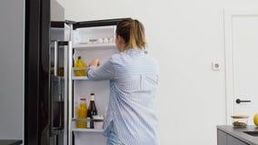 Mujer que toma la manzana de la cocina del refrigerador en casa metrajes