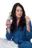 Mujer que toma la píldora Imágenes de archivo libres de regalías