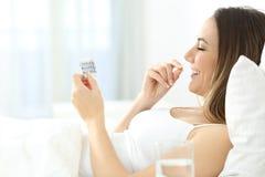 Mujer que toma la píldora anticonceptiva en la cama Fotografía de archivo libre de regalías