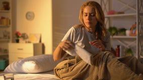 Mujer que toma la p?ldora con agua y que pone la toalla de la compresa en la frente, tratamiento almacen de video