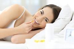 Mujer que toma la píldora del suplemento en la cama por la mañana Imágenes de archivo libres de regalías