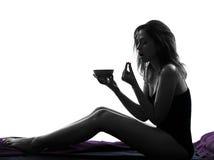 Mujer que toma la píldora de la medicina que se sienta en silueta de la cama Imagen de archivo libre de regalías