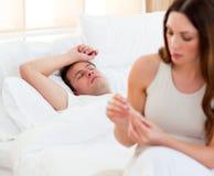 Mujer que toma la temperatura de su marido enfermo Foto de archivo