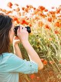 Mujer que toma las fotografías con la cámara en prado imágenes de archivo libres de regalías