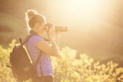 Mujer que toma las fotos al aire libre en una tarde soleada Imagen de archivo libre de regalías