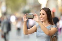Mujer que toma las fotos con un teléfono elegante Imagen de archivo