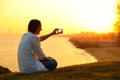 Mujer que toma las fotos con un teléfono elegante en la puesta del sol Imagen de archivo libre de regalías