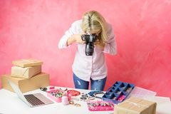 Mujer que toma las fotos de sus propios productos creados para ponerlos en venta en línea imagenes de archivo