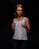 Mujer que toma los antidepresivos Un paciente con las píldoras en un fondo negro Tensión, ansiedad, concepto del tratamiento de l Foto de archivo