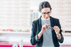 Mujer que toma los vidrios de estante en tienda del óptico Fotografía de archivo