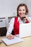 Mujer que toma notas durante una llamada de teléfono Imagen de archivo