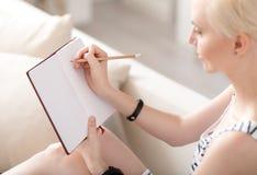 Mujer que toma notas en casa Fotos de archivo libres de regalías