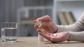 Mujer que toma píldoras contra el dolor de cabeza o el dolor menstrual, tratamiento de la depresión metrajes