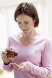 Mujer que toma píldoras de la botella Imagen de archivo