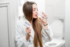 Mujer que toma píldoras en el cuarto de baño Foto de archivo libre de regalías