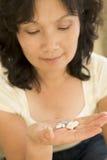 Mujer que toma píldoras Imagen de archivo libre de regalías