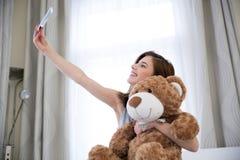 Mujer que toma un retrato del selfie con el oso de peluche Imágenes de archivo libres de regalías