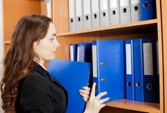 Mujer que toma una carpeta azul del estante Imagen de archivo