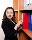 Mujer que toma una carpeta roja del estante Fotografía de archivo