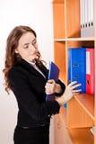 Mujer que toma una carpeta roja del estante Foto de archivo libre de regalías