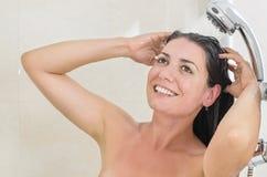 Mujer que toma una ducha imagen de archivo libre de regalías