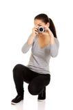 Mujer que toma una foto con una cámara Imágenes de archivo libres de regalías