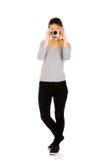 Mujer que toma una foto con una cámara Imagen de archivo libre de regalías
