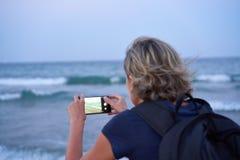 Mujer que toma una foto de un mar en el tel?fono elegante en puesta del sol fotos de archivo libres de regalías