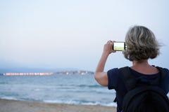 Mujer que toma una foto de un mar en el tel?fono elegante en puesta del sol fotografía de archivo libre de regalías