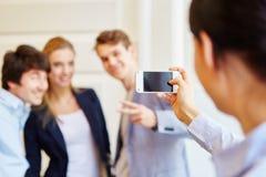 Mujer que toma una fotografía con su smartphone Imagen de archivo libre de regalías
