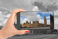 Mujer que toma una imagen con smartphone en Big Ben y el palacio de Westminster, Londres Fotos de archivo libres de regalías