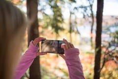 Mujer que toma una imagen de la opinión con el teléfono elegante Imágenes de archivo libres de regalías