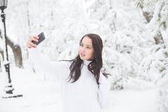 Mujer que toma una imagen del uno mismo en parque del invierno Imagen de archivo libre de regalías