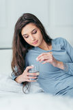 Mujer que toma una píldora Fotos de archivo